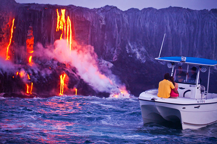 Couple watches lava flowing into the sea. Photo courtesy of Hawaii Tourism Authority (HTA) / Tor Johnson.